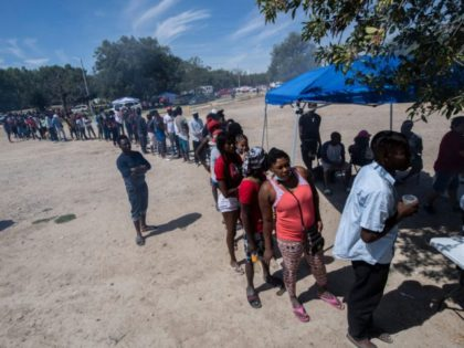 """Haitian migrants queue to get food at a shelter in Ciudad Acuna, Coahuila state, Mexico, on September 21, 2021. - Mexican President Andres Manuel Lopez Obrador urged the United States on Wednesday to act quickly to tackle the causes of the migrant crisis affecting the two neighboring countries. """"Enough talking, …"""