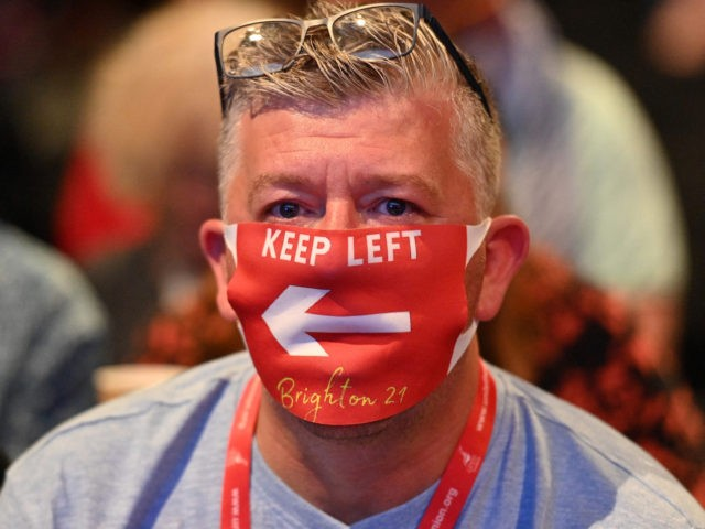A delegate in the audience wearing a face masks listen during the opening day of the annual Labour Party conference in Brighton, on the south coast of England on September 25, 2021. - After the pandemic upended political campaigning, Britain's main parties will aim to reconnect with their members and …