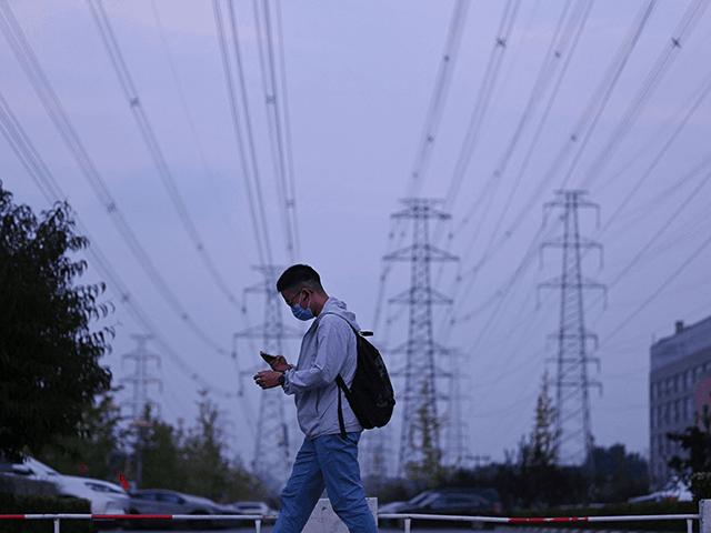 A man walks below power lines in Beijing on September 28, 2021. (Photo by LEO RAMIREZ/AFP via Getty Images)