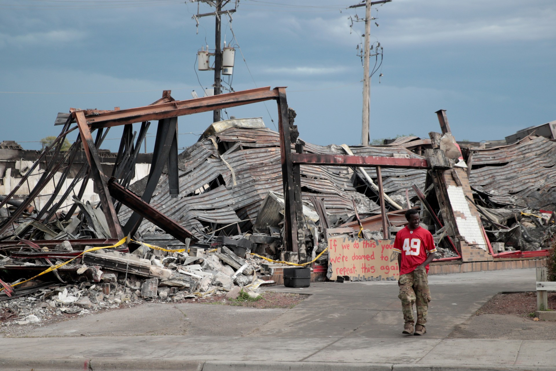 MINNEAPOLIS, MINNESOTA - JUNE 02: A man walk past the charred wreckage of a building destroyed during last week's rioting which was sparked by the death of George Floyd on June 2, 2020 in Minneapolis, Minnesota. Floyd was killed on May 25 while in Minneapolis police custody. Officer Derek Chauvin has been fired from the force, arrested and charged with third degree murder. (Photo by Scott Olson/Getty Images)