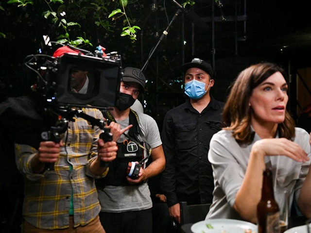"""LOS ANGELES, CALIFORNIA - JULY 01: (L-R) Cameramen Aaron Wise and Rigel """"Che"""" Yaluk film actor Amy Motta during production of the indie feature film, """"The Star City Murders"""" on July 01, 2021 in Los Angeles, California. Effective June 15, 2021, Los Angeles County has retired the health protocols specific …"""