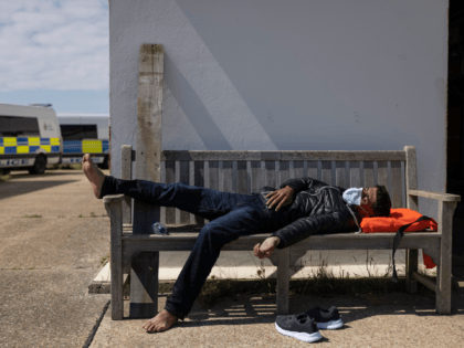 DUNGENESS, ENGLAND - AUGUST 04: A man lays on a bench as a group of around 40 migrants arrive via the RNLI (Royal National Lifeboat Institution) on Dungeness beach on August 04, 2021 in Dungeness, England. UK Home Secretary Priti Patel recently said that the government would seek to criminalise …