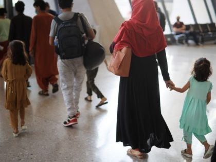 Refugees arrive at Dulles International Airport after being evacuated from Kabul following the Taliban takeover of Afghanistan August 27, 2021 in Dulles, Virginia. Refugees continued to arrive in the United States one day after twin suicide bombings at the gates of the airport in Kabul killed 13 U.S. military service …