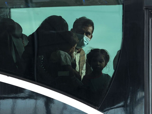 DULLES, VIRGINIA - AUGUST 31: A family looks out the window of a bus at Dulles International Airport that will take them to a refugee processing center after being evacuated from Kabul following the Taliban takeover of Afghanistan on August 31, 2021 in Dulles, Virginia. The Department of Defense announced …