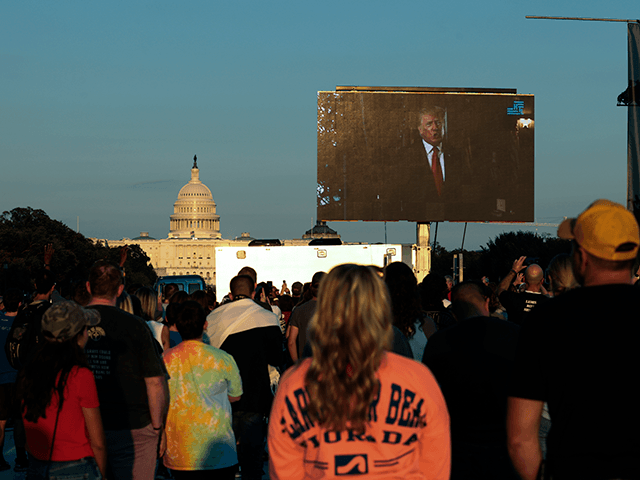 """Attendees watch as a video message from former U.S. President Donald Trump plays during a """"Let Us Worship"""" prayer service on the National Mall on September 11, 2021 in Washington, DC. The nation is marking the 20th anniversary of the terror attacks of September 11, 2001, when the terrorist group …"""