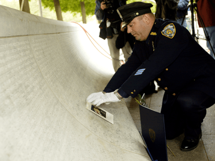New York Police Department (NYPD) police officer James Smith places a photo of his late wife, NYPD police officer Moira Smith, on the National Law Enforcement Officers Memorial in Wasington, DC, 29 April 2002. Tweleve New York law enforcement officers, who were killed in the line of duty during the …