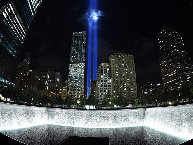 The Tribute in Light illuminates the sky behind the 9/11 Memorial waterfalls and reflecting pool in New York on September 10, 2014, the night before the 13th anniversary of the September 11, 2001 attacks. The tribute, an art installation of the Municipal Art Society, consists of 88 searchlights placed next …