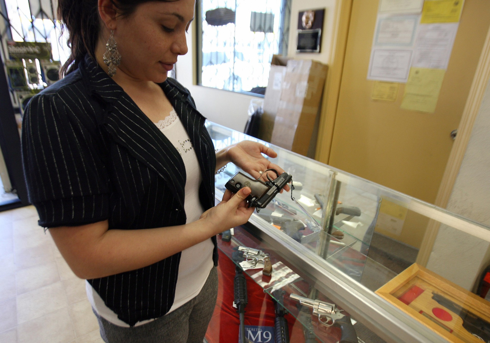 Glendale, UNITED STATES: Aida Khachikyan buys a gun at the Gun Gallery in Glendale, California, 18 April 2007. The massacre at Virginia Tech has ignited fresh talk in the Democratic-led US Congress about tightening US gun laws but it is doubtful enough lawmakers will tackle the politically charged issue. With so many citizens in love with their guns and defensive of their right under the Constitution to keep and bear arms, politicians are reluctant to take on gun owners or the powerful gun lobby. AFP PHOTO/GABRIEL BOUYS (Photo credit should read GABRIEL BOUYS/AFP via Getty Images)