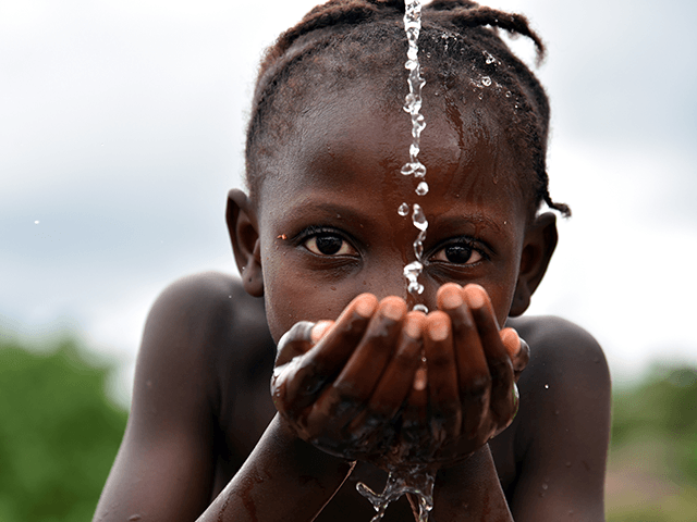 A picture taken on October 12, 2017 shows a student drinking water at the fountain of the Public school of Freeman Reserve in the Todee District, about 30 miles north of Monrovia, in Liberia. / AFP PHOTO / ISSOUF SANOGO (Photo credit should read ISSOUF SANOGO/AFP via Getty Images)