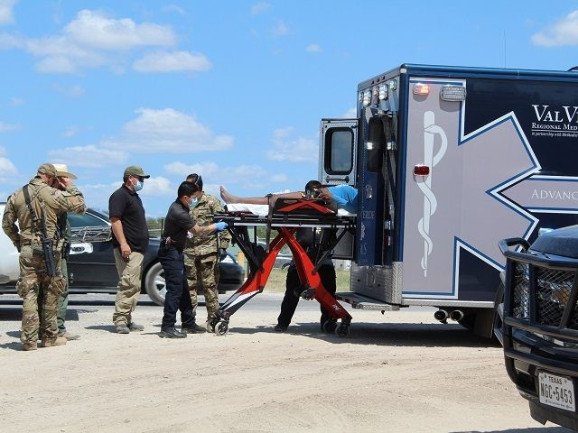 A local ambulance crew loads a woman from the Del Rio migrant camp into an ambulance. (File Photo: Randy Clark/Breitbart Texas)