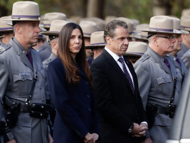 New York Gov. Andrew Cuomo, right and Letizia Tagliafierro, special counsel for public safety, stand with New York State Police before a funeral for Trooper Timothy Pratt on Monday, Oct. 31, 2016, in South Glens Falls, N.Y. Pratt died after being struck by a car while assisting a trucker who …
