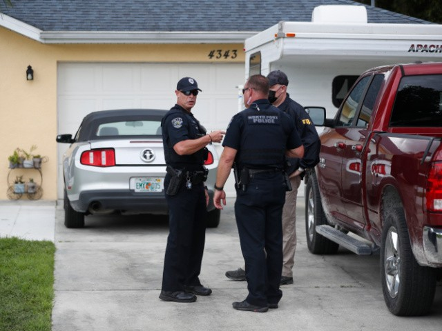 An FBI agent talks with a North Port officer while they collect evidence from the family home of Brian Laundrie, who is a person of interest after his fiancé Gabby Petito went missing on September 20, 2021 in North Port, Florida. A body has been found by authorities in Wyoming that fits the description of Petito, who went missing while on a cross country trip with Laundrie. (Photo by Octavio Jones/Getty Images)