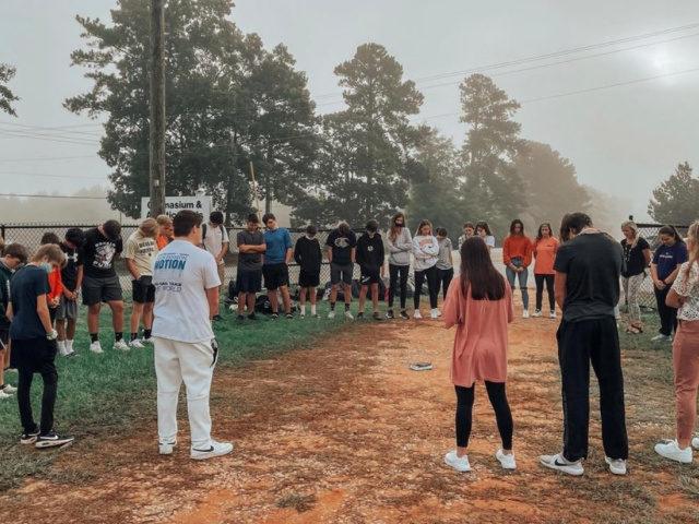 Students Pray Around a Flagpole