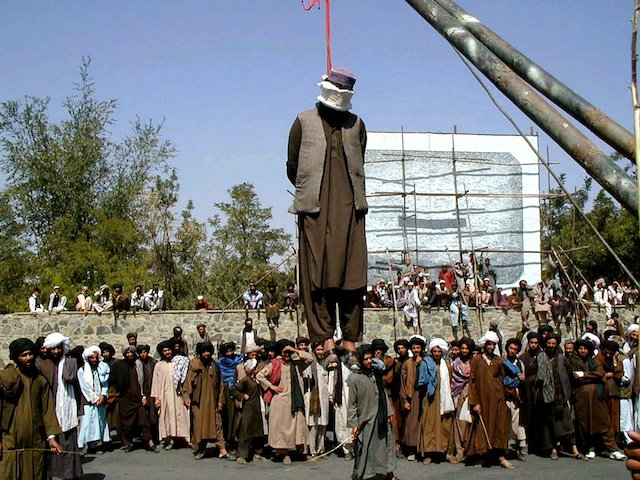 Spectators look at the dead body of Meya Gul, one of two convicted criminal hanged by Talibans in front of a hotel in Kabul, September 23, 2000. (AP Photo/Amir Shah)