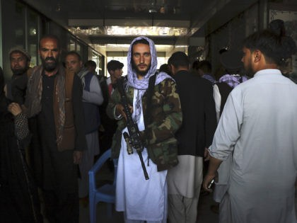 Taliban fighters stand guard bya black market currency exchange at Sarai Shahzada market in Kabul, Afghanistan, Saturday, Sept. 4, 2021. (AP Photo/Wali Sabawoon)
