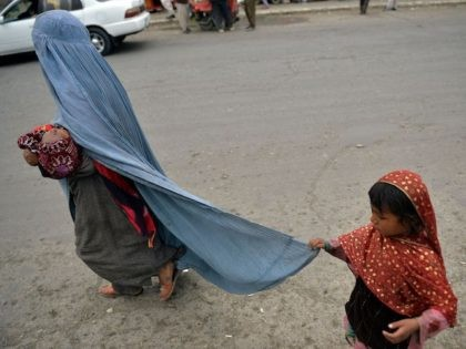 A burqa-clad woman walks with her children along a street in Kabul on August 31, 2021. (Photo by Hoshang Hashimi/AFP via Getty Images)