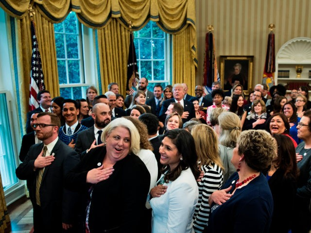 US President Donald Trump stands with teachers and others to say the pledge of allegiance during a national teacher of the year event in the Oval Office of the White House April 26, 2017 in Washington, DC. / AFP PHOTO / Brendan Smialowski (Photo credit should read BRENDAN SMIALOWSKI/AFP via …