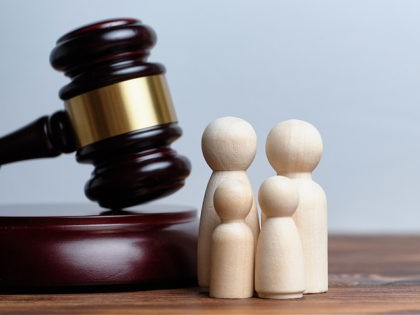 The concept of adopting children by a family. The hammer of a judge with abstract figures of people. - stock photo