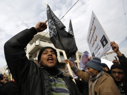 Palestinian Salafist Jihadists wave al-Qaeda-affiliated flags shouting slogans during a protest against the printing of satirical sketches of the Prophet Mohammed by French satirical weekly Charlie Hebdo on January 19, 2015 on their way to the French Cultural Centre in Gaza city. The walls of Gaza's French Cultural Center were …