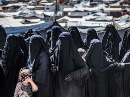 Women and a child queue to receive humanitarian aid packages at the Kurdish-run al-Hol camp, which holds relatives of suspected Islamic State (IS) group fighters, in Syria's northeastern Hasakeh governorate on August 18, 2021. (Photo by Delil SOULEIMAN / AFP) (Photo by DELIL SOULEIMAN/AFP via Getty Images)