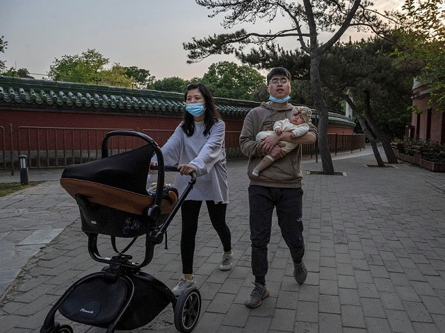 BEIJING, CHINA - MAY 12: A couple carries their newborn baby as they walk at a local park on May 12, 2021 in Beijing, China. According to data released by the government from a national census, China's population grew 0.53 percent over the last 10 years down from 0.57 percent a decade ago bringing the population to 1.41 billion. (Photo by Kevin Frayer/Getty Images)