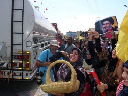 A woman tosses rose petals as people gather to welcome tankers carrying Iranian fuel, upon their arrival from Syria in the city of Baalbeck, in Lebanon's Bekaa valley, on September 16, 2021. - Dozens of tankers carrying Iranian fuel and transported by the Shiite Hezbollah movement arrived from Syria in …