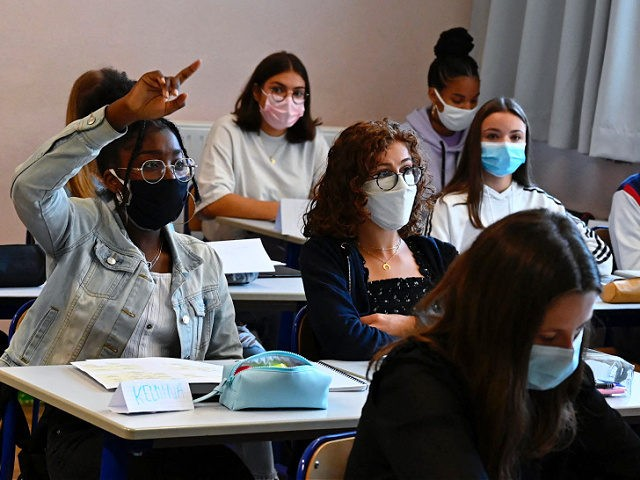 A girl with a protective mask raises his hand as pupils sit in a classroom in Brequigny high school in Rennes, western France, on September 1, 2020 on the first day of the school year amid the Covid-19 epidemic. - French pupils go back to school on September 1 as …