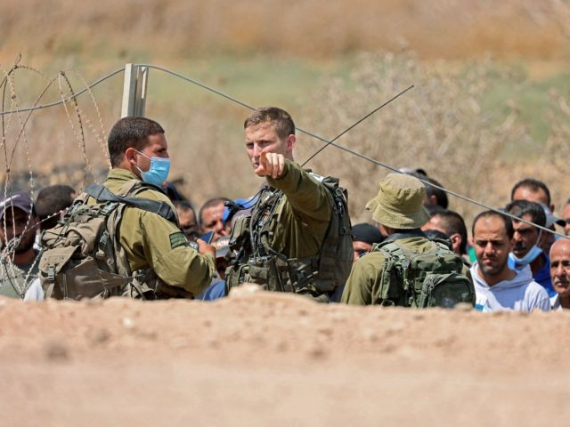 Israeli soldiers search Palestinian labourers, who work in Israel, before allowing them to cross through a hole in a security fence in the West Bank town of Jenin, on September 6, 2021, following the break out of six Palestinians from an Israeli prison. - Six Palestinians broke out of an …