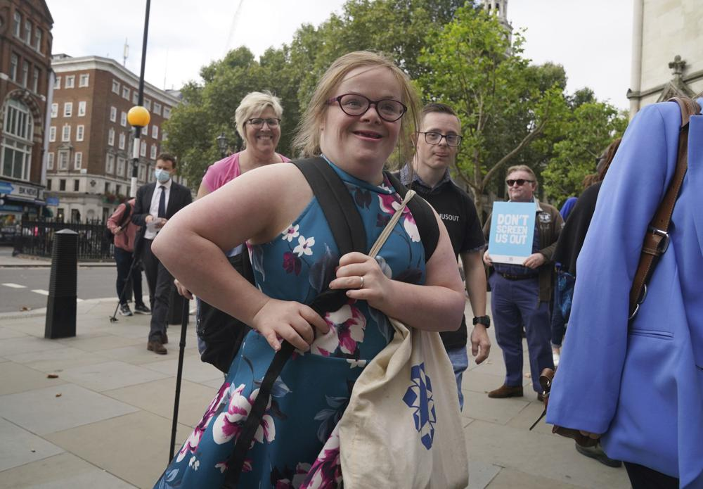 """Campaigner Heidi Crowter arrives at the High Court in London, Thursday, Sept. 23, 2021. A woman with Down's syndrome has lost a court challenge against the British government over a law allowing the abortion up until birth of a foetus with the condition. Heidi Crowter, 26, and two others argued that part of the Abortion Act is discriminatory. Abortions in England, Wales and Scotland are allowed up till 24 weeks of pregnancy, but terminations can be allowed up until birth if there is """"a substantial risk"""" that if the child were born it would suffer from serious abnormalities. (Gareth Fuller/PA via AP)"""