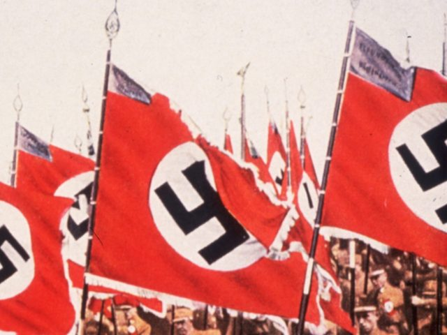1933: The entry of the colours, or Swastikas at the German National Socialist Party Day at Nuremberg. (Photo by Hulton Archive/Getty Images)