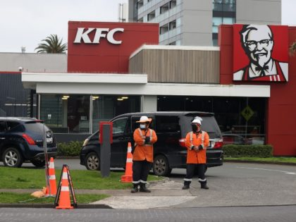 AUCKLAND, NEW ZEALAND - SEPTEMBER 22: Traffic management workers direct a large queue of cars through the KFC drive through in Manukau on September 22, 2021 in Auckland, New Zealand. Restrictions have eased for Auckland residents, with the Greater Auckland area moving to COVID-19 Alert Level 3 settings from 11:59pm …