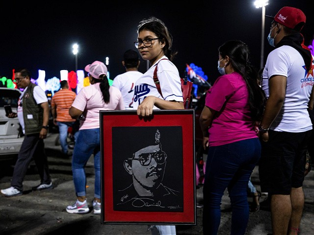 A youth carries a portrait of Nicaraguan President Daniel Ortega during commemorations for the anniversary of the triumph of the 1979 Sandinista Revolution that toppled dictator Anastasio Somoza in Managua, Nicaragua, late Sunday, July 18, 2021. (AP Photo/Miguel Andrés)