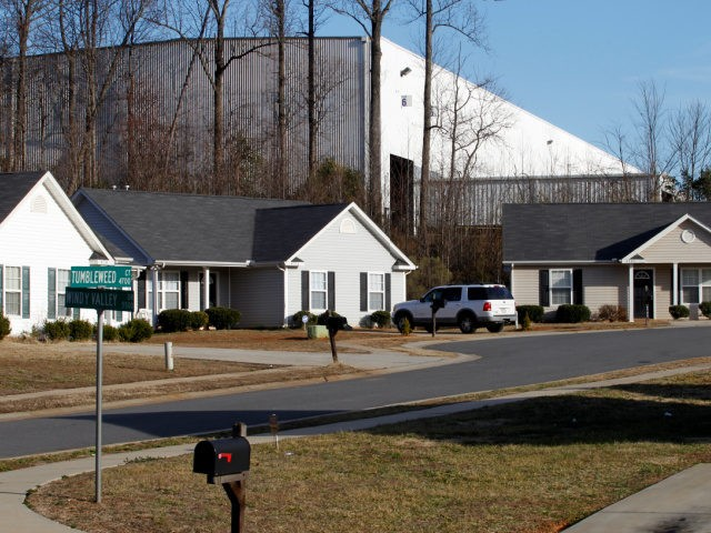 This Tuesday, Feb. 15, 2011 picture shows single family homes in the Windy Ridge subdivision in Charlotte, N.C. and the corner of a large industrial facility at the edge of the neighborhood. Many people sought the American Dream in starter homes here. But in this and a neighboring subdivision is …