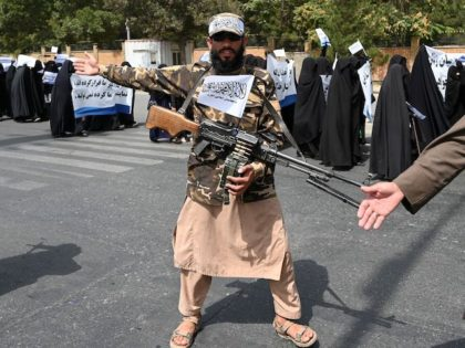 An armed Taliban fighter escorts veiled women as they march during a pro-Taliban rally outside the Shaheed Rabbani Education University in Kabul on September 11, 2021. (Aamir Qureshi/AFP via Getty Images)