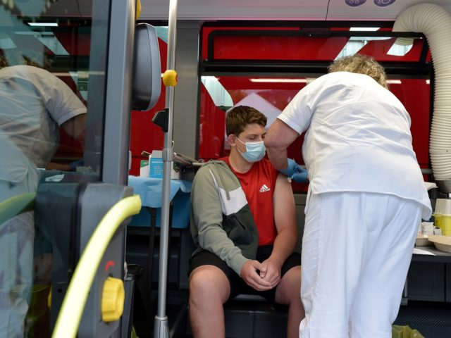 BOLZANO, ITALY - JULY 14: People receive their Covid-19 vaccine in one of two SASA buses equipped as vaccination centers, operating in the small towns of South Tyrol, on July 14, 2021 in Bolzano, Italy. Italy has administered some 58,213,710 doses of Covid vaccines to the population, accounting for 48.3% …