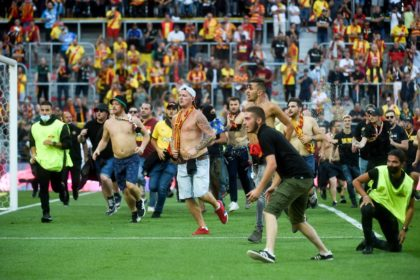 Lens fans run onto the pitch during half-time of the Ligue 1 game against Lille