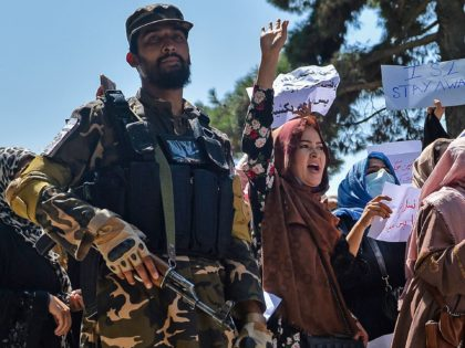 Afghan women shout slogans next to a Taliban fighter during an anti-Pakistan demonstration near the Pakistan embassy in Kabul on September 7, 2021. - The Taliban on September 7, 2021 fired shots into the air to disperse crowds who had gathered for an anti-Pakistan rally in the capital, the latest …