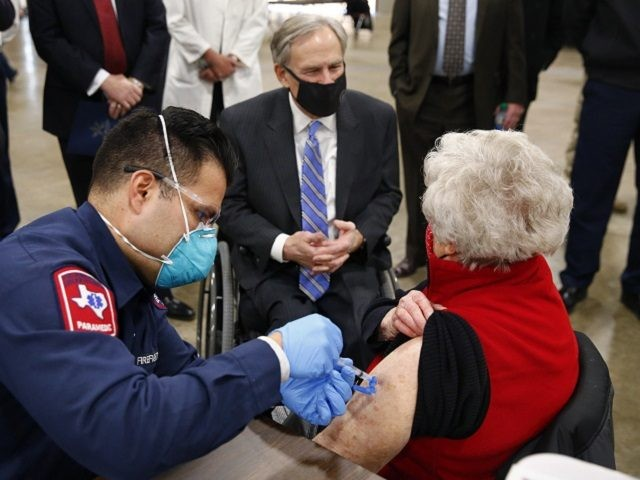 Arlington firefighter Andrew Harris administers a COVID-19 shot to Barbara Alexander of Bedford as she visits with Texas Governor Greg Abbott, center, at a mass vaccination site inside the Esports Stadium Arlington & Expo Center in Arlington, Texas, Monday, Jan. 11, 2021. Alongside local and state officials, Abbott provided an …
