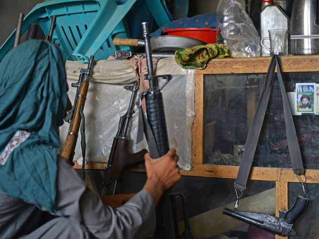 An Afghan vendor displays guns for sale as he waits for customers in his shop at a market in Panjwai district of Kandahar province on September 4, 2021. (Javed Tanveer/AFP via Getty Images)
