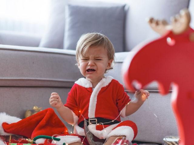 Crying Santa baby boy. Cute baby boy wearing Christmas clothes at home. Merry Christmas. Holiday season. Looking at camera.