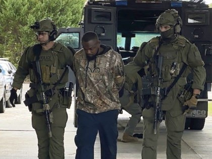In this photo released by Georgia Department of Public Safety, Damien Ferguson, center, is taken into custody by officers of a state SWAT team and a division of the U.S. Marshals Service, October 10, 2021, in Alamo, Georgia. Ferguson is accused of gunning down a Georgia police officer during his …