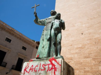 """The statue of the Roman Catholic Spanish priest Junipero Serra is pictured in Palma de Mallorca on June 22, 2020, after it was daubed with graffiti reading """"Racist"""". - The protests against racial inequality and police brutality have seen the toppling or removal of statues depicting Confederate generals, colonial figures …"""