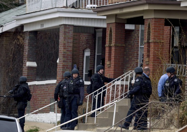 ST. LOUIS, MO - MARCH 8: Law enforcement officials surround a house at the scene where two U.S. marshals and a St. Louis police officer were shot while trying to serve an arrest warrant March 8, 2011 in St. Louis, Missouri. According to the U.S. Marshals Service a gunfight broke …
