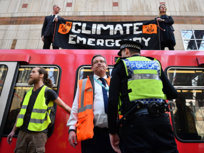 Police stand by as climate change protestors block a DLR train at Canary wharf station on the third day of an environmental protest by the Extinction Rebellion group, in London on April 17, 2019. - Nearly 300 people have been arrested in ongoing climate change protests in London that brought …