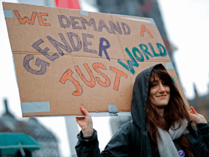 """A woman holds a placard as demonstrators attend the """"March4Women"""" during the International Women's Day in London on March 8, 2020. - Many feminist groups held online campaigns instead of street marches, using hashtags such as #FemaleStrike, #PowerUp and #38InternationalWomensDay to raise awareness of gender inequality. (Photo by Tolga Akmen …"""