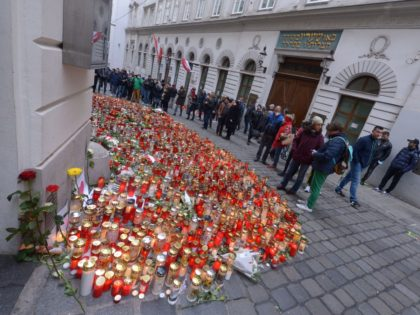 People stand along the Seitenstettengasse in front of the synagogue, where candles commemorate the victims of the terrorist attack at one of the crime scenes, in the centre of Vienna, Austria, on November 8, 2020. - The Austrian government ordered the closure on November 6 of two mosques in the …