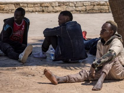 """Subsaharian migants wait near the sea in the northern town of Fnideq as they attempt to cross the border from Morocco to Spain's North African enclave of Ceuta on May 19, 2021. - Spain stepped up diplomatic pressure on Rabat as its prime minister flew into Ceuta, vowing to """"restore …"""