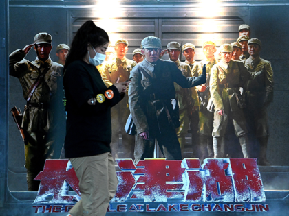 """A woman walks past a movie promotion poster or """"The Battle of Lake Changjin"""" at a mall in Beijing on October 11, 2021. (Photo by Noel Celis / AFP) (Photo by NOEL CELIS/AFP via Getty Images)"""