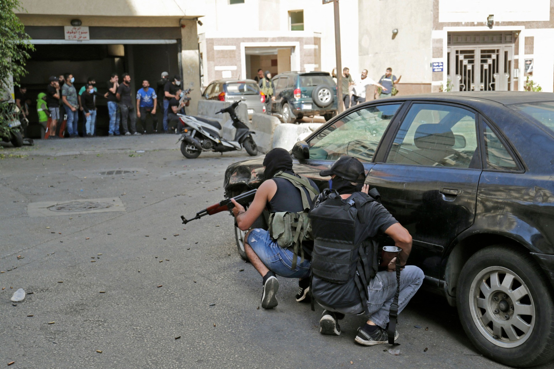 Shiite fighters take cover during clashes in the area of Tayouneh, in the southern suburb of the capital Beirut, on October 14, 2021. - Gunfire killed at least three people and wounded 20 at a Beirut rally organised by the Shiite Hezbollah and Amal movements to demand the dismissal of the Beirut blast lead investigator. (Photo by ANWAR AMRO / AFP) (Photo by ANWAR AMRO/AFP via Getty Images)