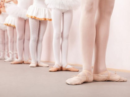 Group of six little ballerinas standing in row behing their ballet teacher and practicing ballet. They are all good friend and amazing dance performers